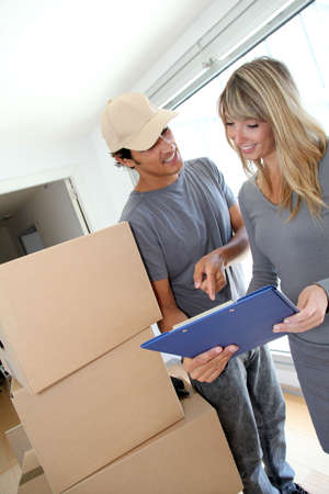 Woman with delivery man checking order contract Stock Photo - 9903370