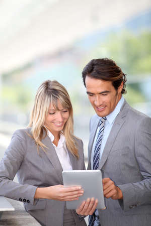 Business team using electronic tablet outside offices building photo