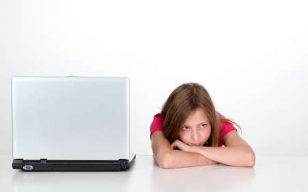 parental control: Girl with thoughtful look next to laptop computer