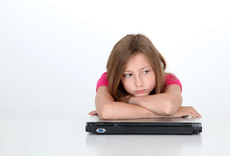 Portrait of sad little girl with laptop computer photo