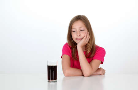 Young girl looking at glass of soft drink photo