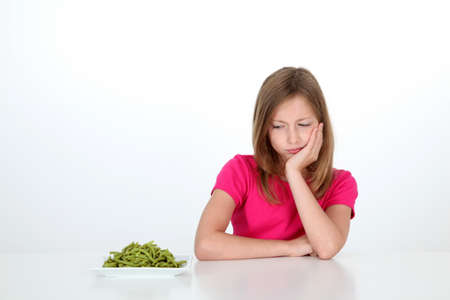 gr�ne bohnen: Young girl looking at plate of green beans with disgust
