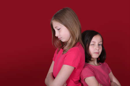 to sulk: Portrait of young girls on red background