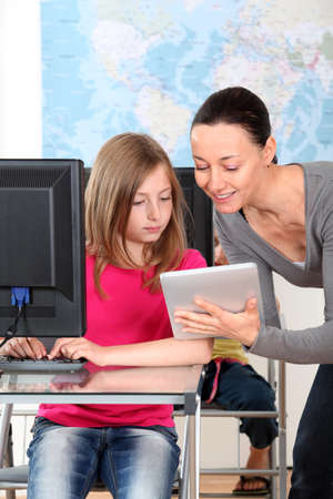 Teacher showing electronic tablet to school girl photo