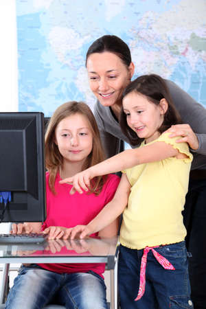 Teacher with kids in front of desktop computer photo
