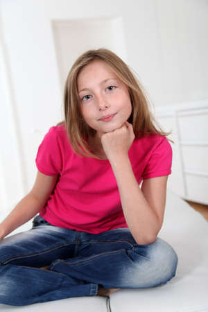 10 years girls: Portrait of blond girl with cross-legged on sofa Stock Photo