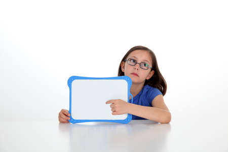message board: Cute little girl holding message board Stock Photo