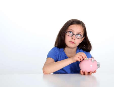 piggybank: Little girl putting coin in piggybank