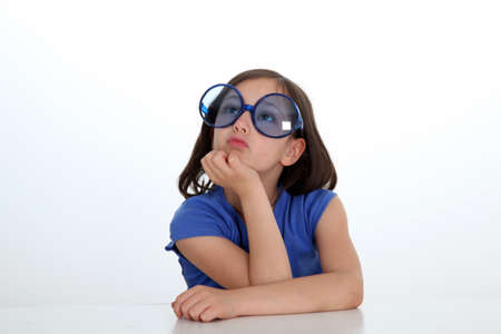 Portrait of little girl with funny sunglasses on photo