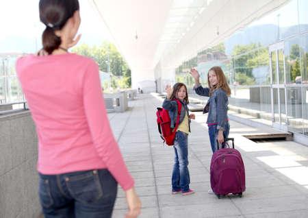 gente saludando: Ni�as de escuela agitando el adi�s a su madre
