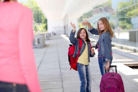 teens school: School girls waving goodbye at their mother Stock Photo
