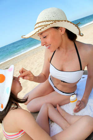 Mother putting sunscreen on her daughters face photo