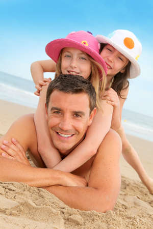 Father with children at the beach photo