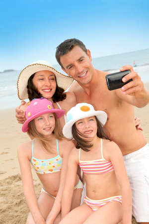 taking photograph: Family taking picture of themselves at the beach Stock Photo
