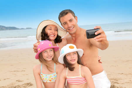 Family taking picture of themselves at the beach Stock Photo
