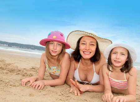 single mother: Mother and daughters lying down the beach Stock Photo