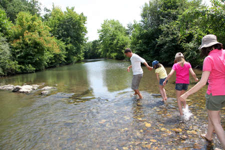 Family crossing river in summer Stock Photo - 9903478