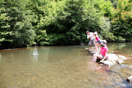 Family playing ricochet in river photo