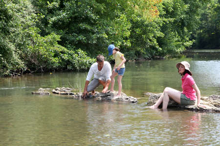 Family sitting in river in summer photo