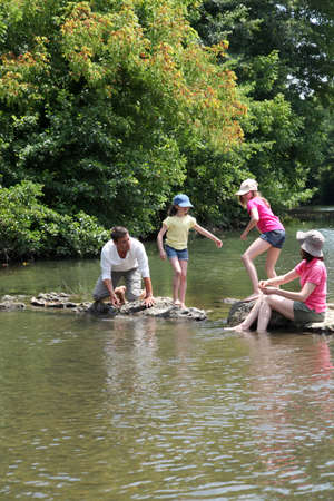 rambling: Family crossing river in summer