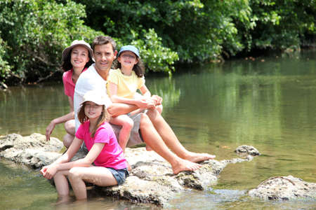 Portrait of family sitting in river in summer photo
