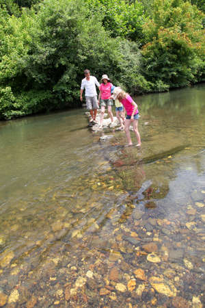 Family crossing river in summer photo