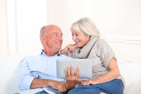 seniors homes: Senior couple using electronic tablet at home Stock Photo