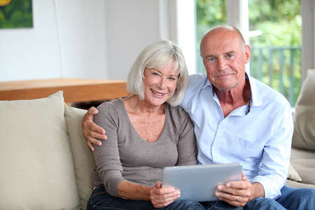 Senior couple using electronic tablet at home photo