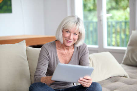 Porrtait of senior woman using electronic tablet at home photo