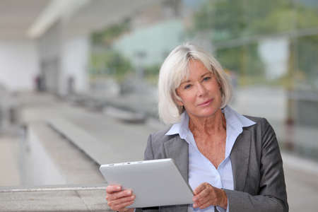 Businesswoman using electronic tablet outside airport photo