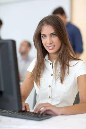 desktop computer: Portrait of student in front of desktop computer