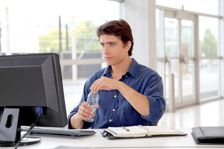 computer training: Office worker drinking water in front of desktop computer