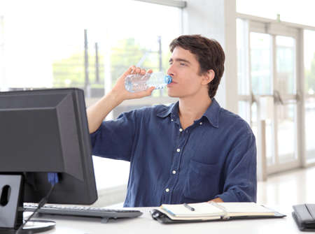 Office worker drinking water in front of desktop computer photo