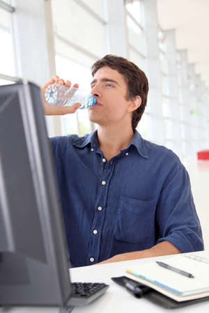 Office worker drinking water in front of desktop computer Stock Photo - 10013360