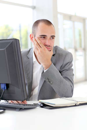 Businessman in front of desktop computer with thoughtful look photo