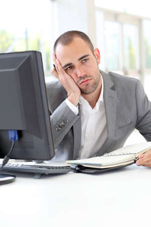 bored man: Portrait of exhausted businessman in office
