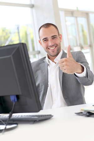 desktop computers: Happy businessman showing thumbs up