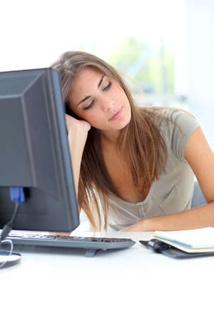 Exhausted young woman sitting in front of computer photo