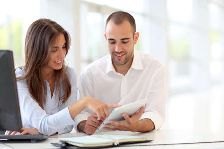 finance girl: Young adults in training course using touchpad Stock Photo