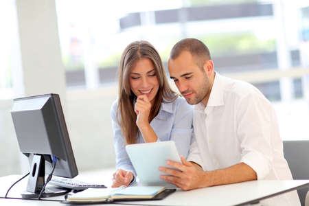 training course: Young adults in training course using touchpad Stock Photo