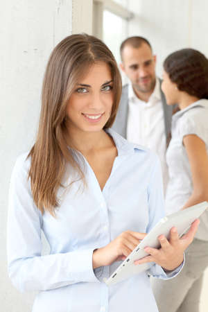 Young woman using electronic tablet in meeting photo