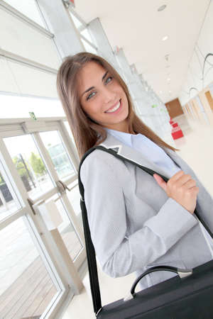 Beautiful young woman standing in hall with briefcase Stock Photo - 10013546