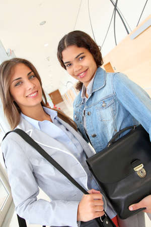 College students standing in hall with briefcase photo