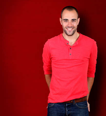 textspace: Handsome man standing on red background Stock Photo