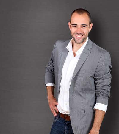 businessman standing: Cool businessman standing on grey background