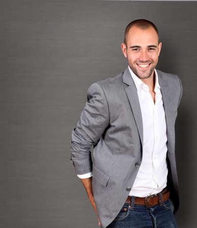 uomo felice: Businessman standing fresco su sfondo grigio
