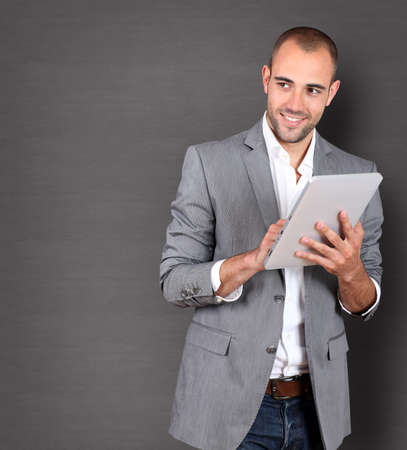 Cool businessman using touchpad on grey background photo