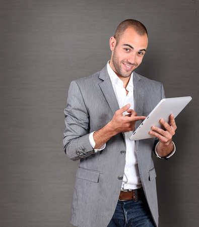 textspace: Cool businessman using touchpad on grey background