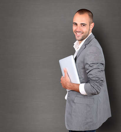 adult wall: Cool businessman using touchpad on grey background