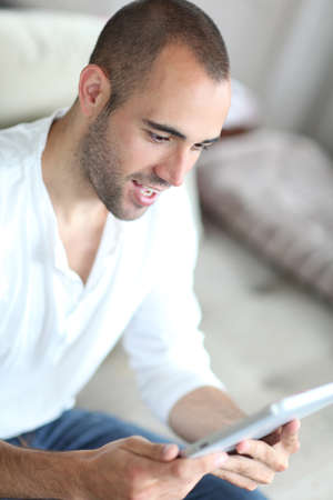 Closeup of handsome man websurfing on touchpad Stock Photo - 10013253